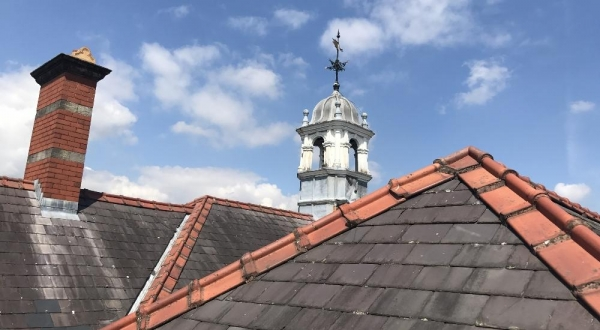 Slate roof, chimney and lead-clad turret with weather vane.